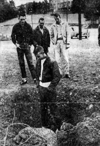 Four youths stand in a hole blown in the Spruce Pine baseball field on the evening of December 31,1959