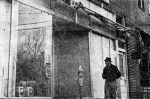 A man walks by the boarded-up window in the store front of Western Auto on Locust Avenue after the blast.