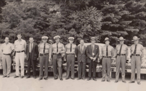 Mitchell County's law enforcement community poses for this picture circa 1960. Left to right are: James Edwards, Mitchell County Deputy, Joe Stewart, Mitchell County Deputy, Sam Gouge, Mitchell County Sheriff, Jim Burleson, Chief of Police, Ray Gunter, Spruce Pine Police, Cotton Burleson, Spruce Pine Police, Herb Teague, Detective Spruce Pine, Zeke Howell, Mitchell County Jailer, Charlie Radcliffe, NC Highway Patrolman, R. E. Pipes, NC Highway Patrolman, Lee Lance, NC Highway Patrolman.