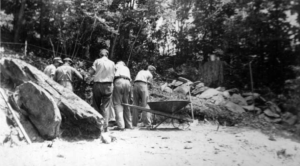 Local men, led by Lester McKinney, constructed and kept up Camp As-You-Like-It. Here, they are building a wall with rocks gathered from the Linville Gorge and Grandfather Mountain. The qual- ity of their work was outstanding, but vandals destroyed much of the stonework after the camp's closure. Some examples remain hidden deep in the woods.