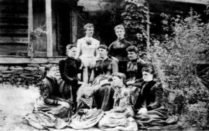 Isaac English's daughters posed in front of the English Inn for a portrait, circa 1889. Mary is in the middle, with the others clockwise from top left, Orah, Minnie, Josephine (Dotie), Sarah (Sadie), Cordelia (Cordie), Mabel, Emma, and Illia.