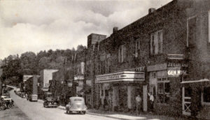 """Spruce Pine's first theater was not the Carolina. The Piedmont Theatre, which was originally located on Lower Street where Dellinger's Christian Bookstore is today, was opened in 1928 by John Taylor. The theater originally hosted silent movies and featured a large pump organ that provided musical accompaniment. It later switched to """"talkies"""" and served as a stage for dance and music recitals. The Piedmont also hosted fundraisers for the Spruce Pine Band when it traveled to the state competition in Greensboro. On January 1, 1938, the Piedmont closed when its equipment and contracts were purchased by the Cherokee Amusement Company, which had opened the Carolina Theatre just before Christmas in 1937. As part of the sale, Taylor agreed to shutter the business and not operate a playhouse in the vicinity for a period of 10 years. There were several times when folks in Spruce Pine had two theaters to choose from. The Baker Theater on Oak Avenue provided the latest Hollywood films as well. This photo was made in the 1930s, when the Piedmont still had a presence on Lower Street."""