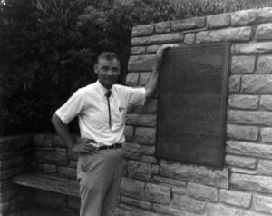 Dr. Harley Jolley, professor emeritus of history at Mars Hill University, stands next to the plaque honoring the Overmountain Men at the North Carolina Museum of Minerals at Gillespie Gap. When Hwy 226 was built through the gap, the monument was razed, but the plaque was placed on a new monument beside the museum in the 1950's.