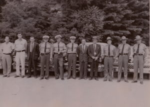 "This photograph shows the Mitchell County Law Enforcement team about 1960. Pictured, left to right, are James Edwards and Joe Stewart, Mitchell County deputies; Sam Gouge, Mitchell County Sheriff; Jim Burleson, Spruce Pine Chief of Police; Ray Gunter and Landon ""Cotton"" Burleson, Spruce Pine Police Department officers; Herb Teague, Spruce Pine Police Department detective; Zeke Howell, Mitchell County Jailer; and North Carolina Highway Patrolmen Charles Radcliffe, R.E. Pipes, and Lee Lance. The automobiles, left to right, have been identified as a 1960 Ford, a 1960 Pontiac, a 1959 Chevrolet, and a 1959 Ford."