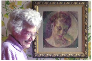Aunt Mickey standing in front of a portrait of her reading a book, by her husband, Paul W. Whitener, who passed away in 1959, 23 years after their marriage in 1936.